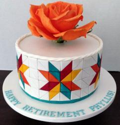 Retirement Cake in White Round Shape with Large Orange Flower on Top & Triangular Patterns.JPG