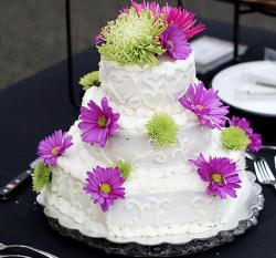 Small 3 tier white wedding cake with heart shapes and fresh purple green flowers.JPG