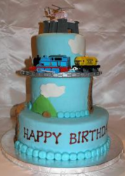 Light blue three tiers with Thomas running on the train tracks and Harold on the top of the cake.PNG