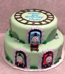 Light green Thomas and friends coming out from the sheds with train tracks on the cake topper images.PNG