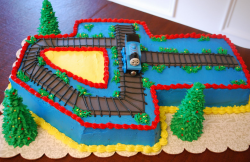 Thomas the train on train tracks with cake shaped number 4.PNG