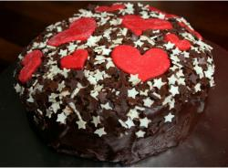 Chocolate cake decorating for valentines day with white stars and red hearts decor.JPG