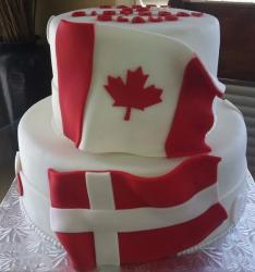 Two tiers fancy Danish birthday cake or Danish wedding cake with large Canadian flag and Danish flag decor.JPG