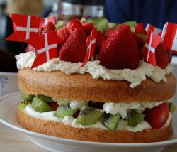 Danish traditional birthday cake filled with fresh fruits and decorated with fresh strawberries and kiwifruit and Danish flags.J