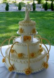 Tri-tier ivory round wedding cake with yellow arches yellow roses ceramic bride groom topper.JPG