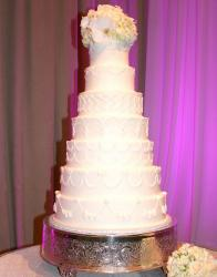 Seven tier white wedding cake with white rose flower bouquet on top.JPG