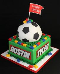 Square lego birthday cake with scoccer ball and the flag with some lego blocks on top.JPG