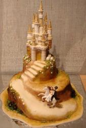Castle theme wedding cake with bride and groom on white steed.JPG