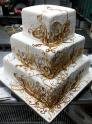 Cool three tier square wedding cake with golden swirls.JPG