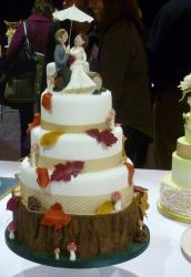 Fall Foliage Theme 3 Tier Wedding Cake with Topper of Groom Holding Umbrella for Bride.JPG