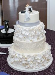 4 tier White Wedding Cake with Bride Groom Toppers Sitting in Romantic Pose.JPG