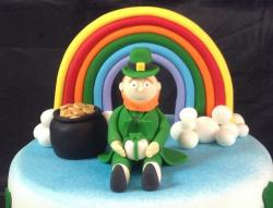 St. Patrick's Day Cake decor with Irish man with rainbow behind and a pot of gold at the end of the rainbow.JPG