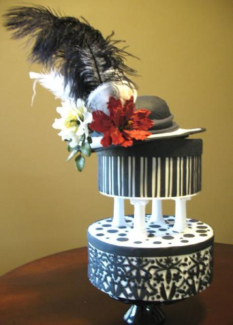 Two tier black and white cake with feathers and hat.JPG