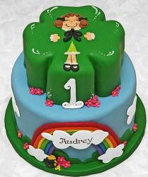 Two tiers St. Patricks cake with the top cake shaped of a clove and the bottom cake round and blue sky with rainbow.JPG