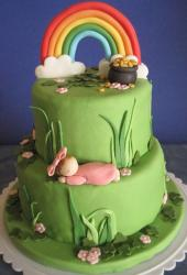 Two tiers with with rainbow and golden pot and cute baby girl perfect for St Patrick Christening cake.JPG