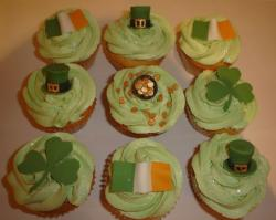 Vanilla cupcakes with light green frosting and super cute cupcake topper with cloves, St Patrick hats and Irish flags.JPG