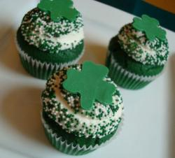 Green St Patricks cupcakes with white and green sprinkles with large cloves cupcake decor.JPG