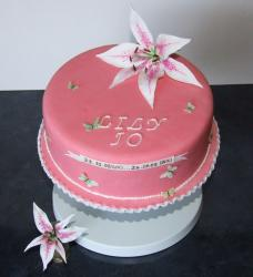 Round pink Christening Cake with lily topper