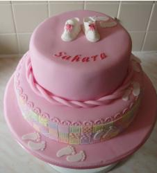 Two pink Christening Cake photos with cute white baby shoes topper