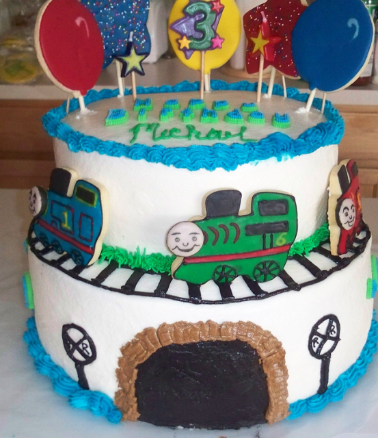 Two tiers with train cake decor and balloons.PNG
