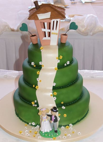 Green Four Tier Wedding Cake With Cottage On Top And Bride