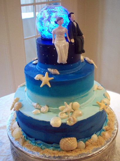 Three tier blue wedding cake with sea shells and crystal ball.JPG