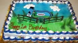 Thomas the train birthday cake with Thomas running on the rails with fences.PNG