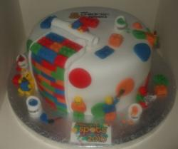 Fancy lego birthday cake with white round cake and lots of lego blocks and figures.JPG