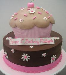 Two tier birthday cake with big cupcake on top.JPG