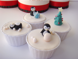 Christmas cupcakes with pingwins playing with snow balls and gifts.PNG