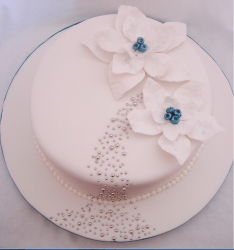 Snow white Christmas cake with christmas flowers in total white with blue centers.PNG