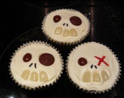 Three skeleton cupcakes with chocolate eyes and candy teeth.JPG