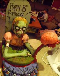Zombie birth cake with Female zombie coming out from a graveyard holding a brain.JPG