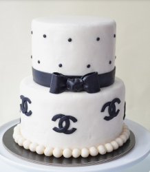 Two tiers white cake with black dots cake decor and black bow and chanel logo.PNG