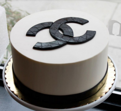 White round Chanel cake with large Chanel logo cake topper.PNG