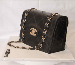 Realistic looking Chanel handbag with gold strap cake with gold Chanel logo.PNG