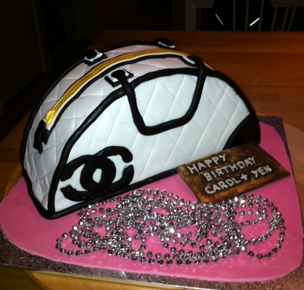 Fancy designer handbags birthday cakes picture of Chanel handbag in white with black patterns and black Chanel logo and some bli