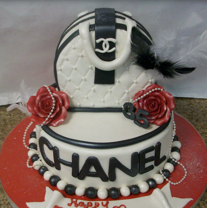 Large fancy white and black Chanel cakes with large Chanel purse with red cake roses with pearls.PNG