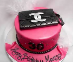 Newest designer handbags cake in hot pink with black Chanel clutch with white Chanel logo perfect for birthday parties.PNG