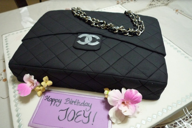 5d97c5f51ac9 Black Chanel purse cake with gold chain strap.PNG
