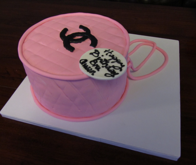 Pink Chanel purse cake with black Chanel logo.PNG