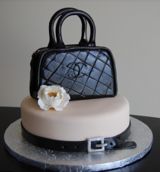 Trendy Chanel cake with black Chanel purse cake topper and flower.PNG