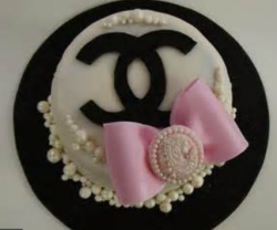 Fancy Chanel birthday cake in white with black Chanel logo and large cake bow.PNG
