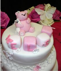 Christening white two tier with pink teddy bear topper with cubes in white and pink
