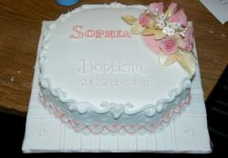 White Christening cake with pinkish floral topper