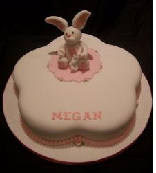 Flower shaped Christening cake with white and light pink rabbit topper
