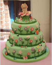 Three tier green christening cake with colorful flowers picture