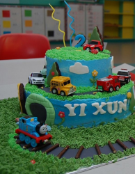 Kids fany birthday cake with Thomas the train cake theme with two tiers and cars while Thomas running on the rail tracks.PNG