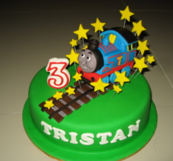 Green trendy Thomas the train cake running on the train traks with stars.PNG