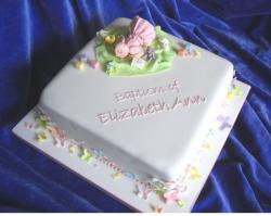 White square christening cake with doll topper